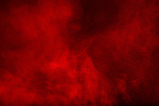 Red powder cloud against dark background