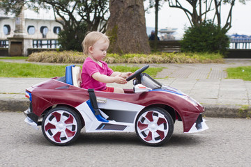 Baby girl riding on small car