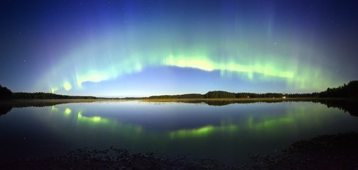 Northern lights panorama with reflection on the lake at night.