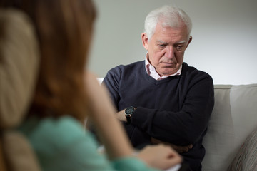 Psychologist listening senior man