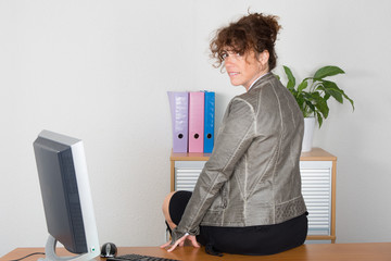 Joyful and smiling mature professional business woman in an office space, sitting on her desk