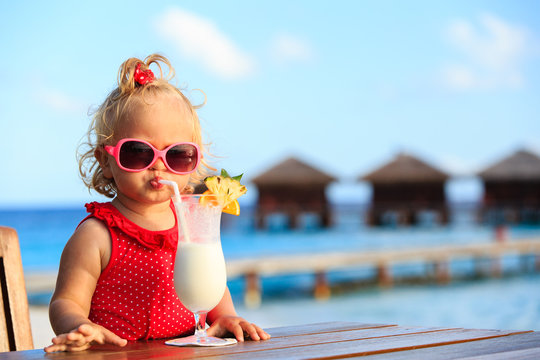 cute little girl drinking cocktail on tropical beach