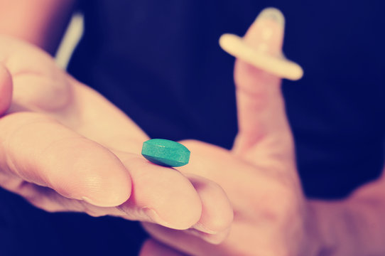 young man with blue pill and condom, filtered