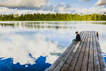 Boy sitting on a wooden pier and watching the water