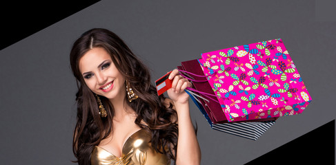 Young woman with shopping bags and credit card on a gray
