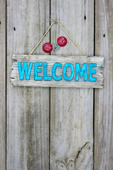 Welcome sign with bottle caps hanging on rustic wood door