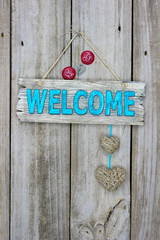 Welcome sign with hearts and bottle caps hanging on rustic wood door