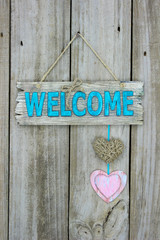 Welcome sign with hearts hanging on rustic wood door