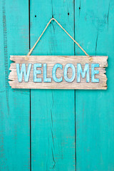 Welcome sign hanging on antique teal blue rustic door