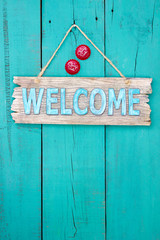 Welcome sign with bottle caps hanging on teal blue door