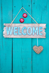 Welcome sign with heart  and bottle caps hanging on teal blue door