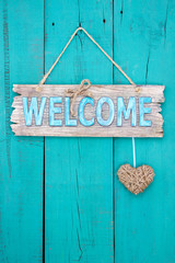 Welcome sign with heart hanging on teal blue door