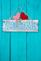 Welcome sign with hearts hanging on teal blue door