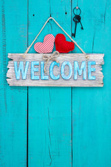 Welcome sign with hearts and keys hanging on teal blue door