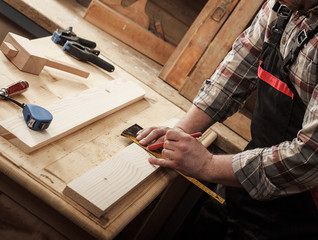 Carpenter marking a measurement on a wooden plank.