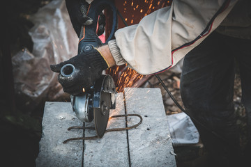 Cutting metal wire with angle grinder, sparks from the disk