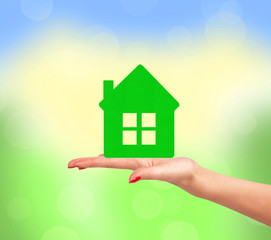 Female hand with small model of house over bright nature backgro