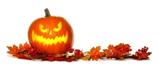 Illuminated Halloween Jack o Lantern with border of red autumn leaves isolated on a white background