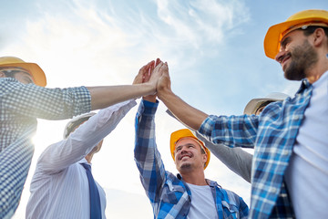 close up of builders in hardhats making high five
