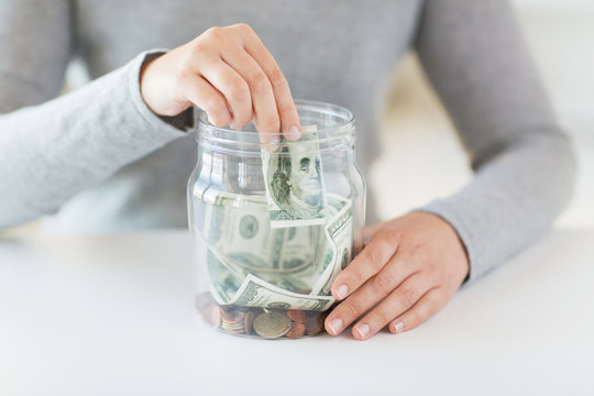 close up of woman hands and dollar money in jar