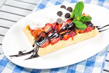 Belgium waffles with chocolate sauce, ice cream and strawberries
