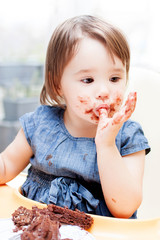 An adorable little girl enjoying her birthday cake.