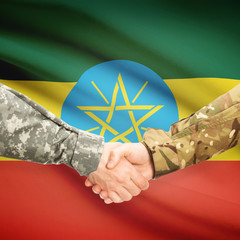 Men in uniform shaking hands with flag on background - Ethiopia