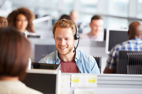 Young man working at a computer in a call centre