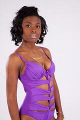 Pretty black woman in purple swim suit, looking thoughtful