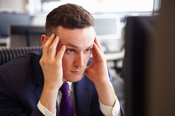 Head and shoulders of a young stressed businessman, head in hand