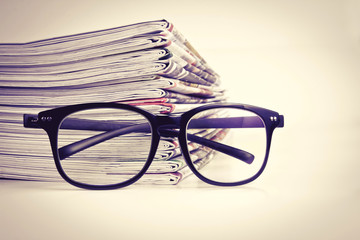 selective focus on reading eyeglasses with stacking of newspaper