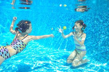 Children swim in pool underwater, happy active girls have fun in water