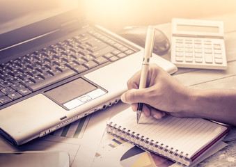 Busy business woman hand holding pen and writing on notebook