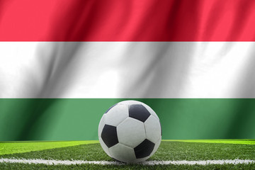 Soccer ball and national flag of Hungary lies on the green grass