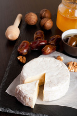 Camembert with honey, dates and nuts on dark background