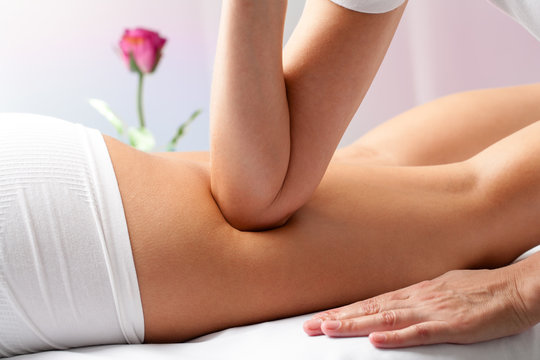 Therapist massaging female thigh with elbow.