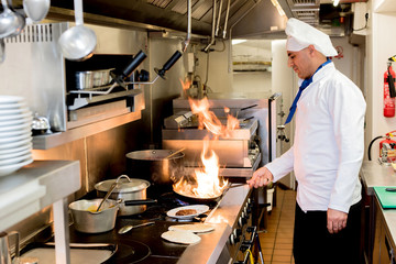 Chef with burning flames on kitchen