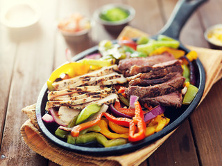 Wall Mural - mexican food - skillet fajitas with steak and chicken on rustic wooden table