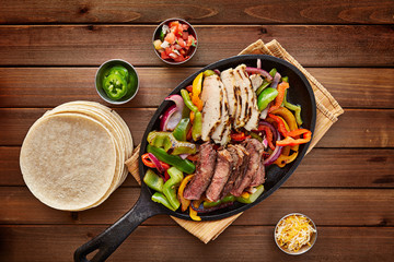 mexican steak and chicken fajitas in cast iron skillet shot top down with corn tortillas