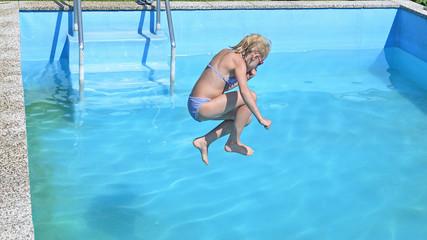 Kind springt in den pool