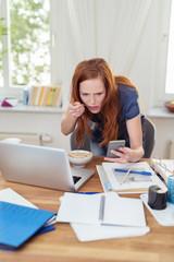 gestresste frau mit computer und handy zu hause
