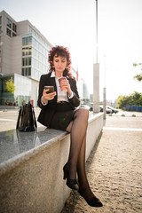 Coffee break - senior business woman with phone in street