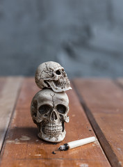 Skull and cigarette on wooden floor with grunge background
