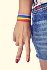 woman making the V sign, with a bracelet patterned as the rainbo