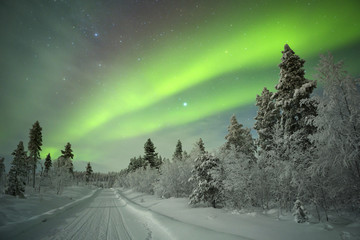 Aurora borealis over winter landscape in Finnish Lapland.