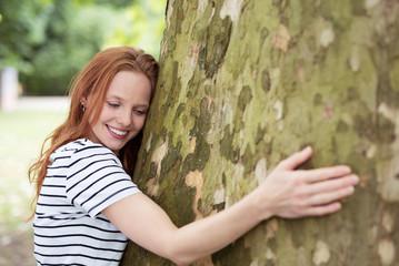 lächelnde frau umarmt einen baum im park