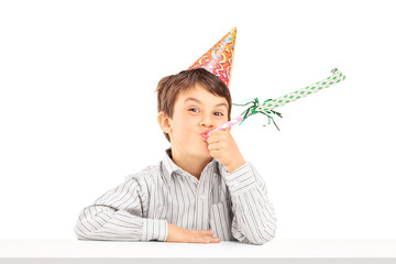 Little kid with party hat blowing a favor horn