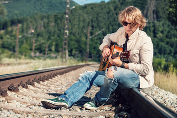 Young man with guitar on the railway