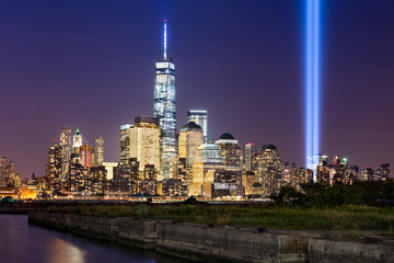 Wall Mural - New York City Tribute in Light. The annual commemoration of September 11th in Lower Manhattan adjacent to the new World Trade Center. Two vertical columns of light rise above the Financial District.