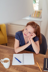 entspannte frau sitzt zuhause am tisch und schreibt etwas auf